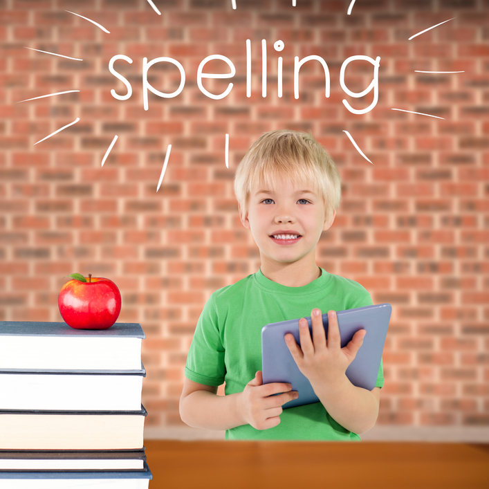 The word spelling and cute boy using tablet against red apple on pile of books